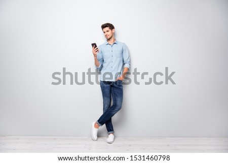 Full size photo of concentrated smm worker man use cellphone answer sms messages have online conversation with friends type comments posts wear stylish outfit sneakers isolated grey color background