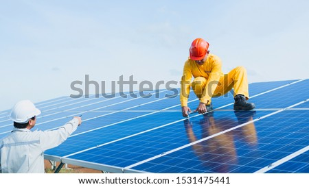 engineer or electrician working on  maintenance equipment at industry solar power;  engineer using thermal imager to check temperature heat of solar panel  #1531475441