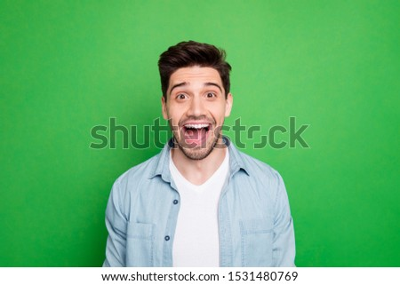 Close up photo of amazing macho guy revealing perfect white teeth looking on unbelievable low prices wear casual denim shirt isolated over green color background