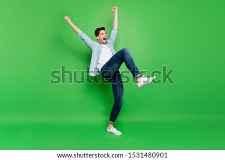 Full body profile photo of carefree crazy guy yelling celebrating favorite football team victory raise fists and leg wear denim shirt isolated green color background