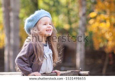 Portrait of a beautiful little girl in a blue beret. A child walks in a beautiful autumn park. #1531498655
