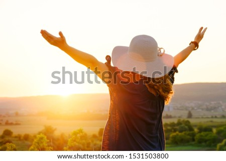 The silhouette of a happy woman in a dress and hat standing in a beautiful landscape field on a background of bright sunset and admiring nature, raising her hands to the sun. Lens flare. Lifestyle #1531503800