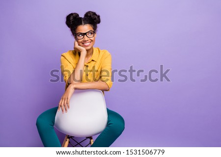 Photo of amazing dark skin lady sitting cozy on chair looking wondered side empty space wear specs yellow shirt trousers isolated purple color background