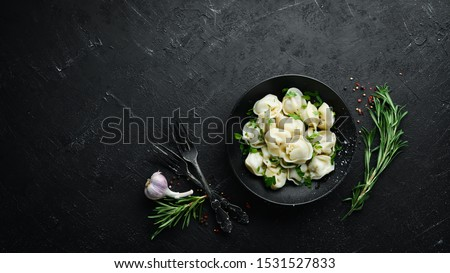 Russian pelmeni meat Dumplings with greens in a black plate. Russian traditional cuisine. Top view. Free copy space. #1531527833