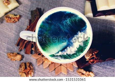 White cup with water. Sea. Ocean. Sea waves. Creative postcard. #1531531061