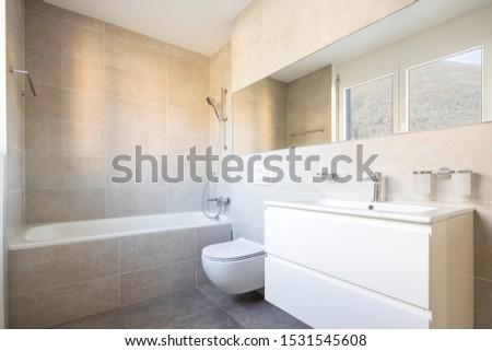 Modern minimal bathroom with large tile bathtub. Nobody inside #1531545608