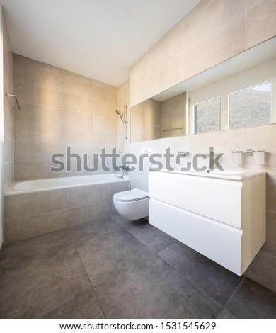 Modern minimal bathroom with large tile bathtub. Nobody inside #1531545629