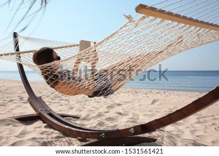 Young woman reading book in hammock on beach #1531561421
