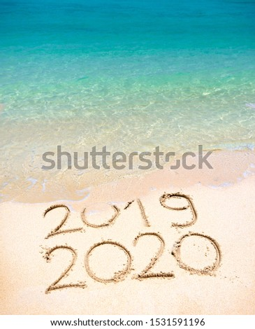 End of 2019 Happy New Year 2020, lettering on beach with wave and clear blue sea on sunny day. Handwritten inscription 2019 and 2020 on beautiful golden sand beach. New Years 2020 replace 2019 concept #1531591196