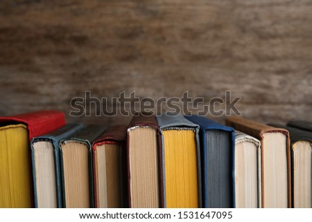Stack of hardcover books on wooden background. Space for text #1531647095
