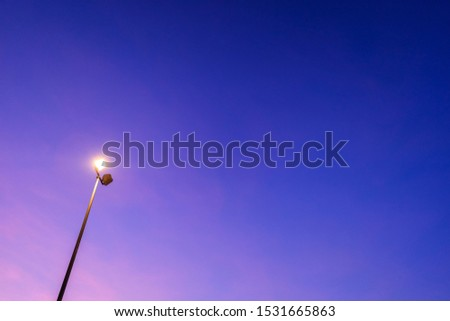 Blue sky at dusk illuminated with a lamppost. #1531665863