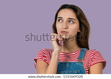 Portrait of a beautiful girl in a striped T-shirt, looks aside with pensive expression, is considering a plan for further action. #1531669328