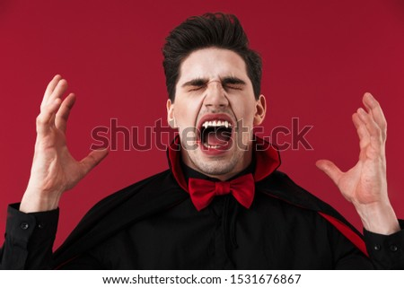 Image of angry vampire man with blood and fangs in black halloween costume screaming isolated over red wall