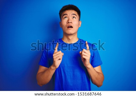 Young asian chinese man wearing t-shirt standing over isolated blue background amazed and surprised looking up and pointing with fingers and raised arms. #1531687646