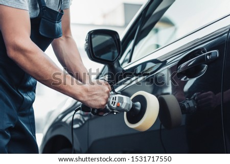 partial view of car cleaner polishing car door with buffer machine #1531717550