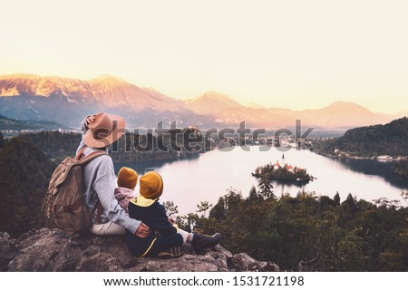 Journey Slovenia with kids. Family travel Europe. Hiker woman with children on Bled Lake among nature and Alps mountains. Traveling mother with backpack with her kids at autumn or winter vacation #1531721198