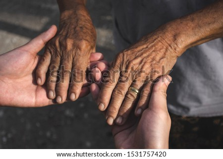 Young woman hands holding elderly person's hands. #1531757420