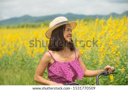 happy young woman enjoying summer in yellow field at sunset, outdoor portrait of a beautiful middle aged woman walking with bicycle. attractive sexy girl in a field with flowers. #1531770509
