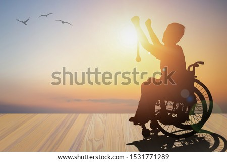 Disabled person silhouette winners hand holding gold medal top of wheelchair have sunset with mountain background. International Disability Day or Handicapped Paralympics. Challenge, Conquer concept. #1531771289