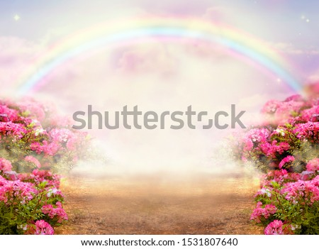 Fantasy panoramic photo background with pink rose garden, misty path leading to fabulous rainbow unicorn house. Idyllic tranquil morning scene and empty copy space. Road goes across hills to fairytale Royalty-Free Stock Photo #1531807640