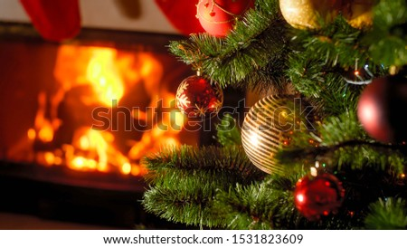 Background of burning fireplace and decorated Christmas tree with baubles and garlands #1531823609