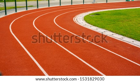 Red running track or resin Emboss Topping with white lines in outdoor sport stadium, side is a field and park. Backgrounds and rubber texture. #1531829030