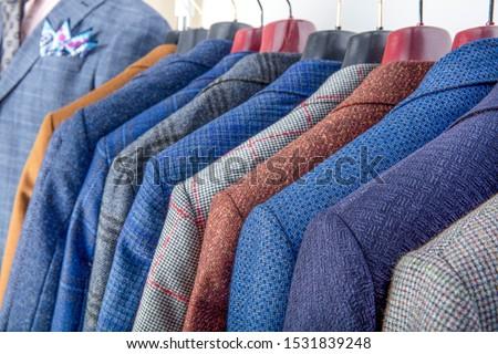 Men's jackets on hangers in the men's store. Row of men's suit jackets hanging in closet. #1531839248