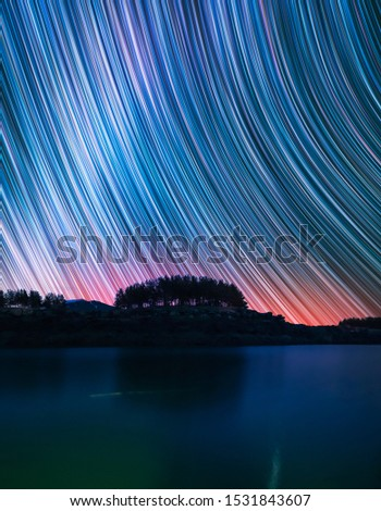 Night landscape. Beautiful lake and forest. Behind the fir forest starry sky with star trail. Timelapse photography.