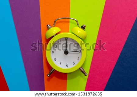 Retro alarm clock on colorful bright stripes on colored paper lines. Art. #1531872635