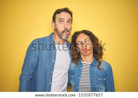 Beautiful middle age couple together wearing denim shirt over isolated yellow background making fish face with lips, crazy and comical gesture. Funny expression. #1531877657