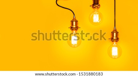 Vintage fashionable edison lamp on bright yellow background. Top view flat lay copy space. Creative idea concept, designer lamp, modern interior item. Lighting, electricity, background with lamp #1531880183