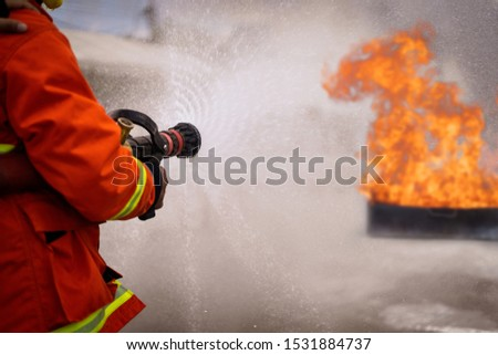 In to the fire,Brave firefighter using extinguisher and water from hose for fire fighting,  Firefighters training, foreground is drop of water springer. #1531884737