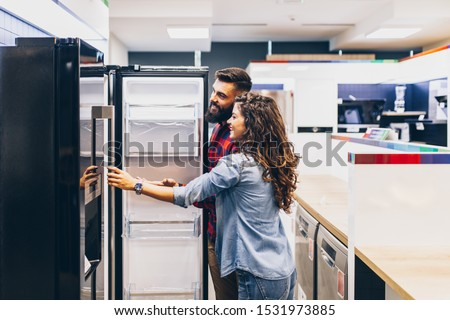Young couple, satisfied customers choosing fridges in appliances store. #1531973885
