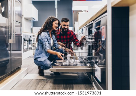 Beautiful and happy young couple buying dishwasher in modern appliances store. #1531973891