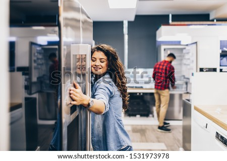 Young couple, satisfied customers choosing fridges in appliances store. #1531973978