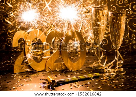 A close up view of the numbers 2020 for Happy New Year celebration with sparklers in the background and two wine glasses on the side.  #1532016842