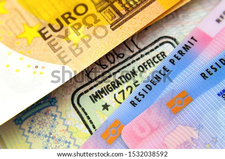 UK Biometrical Residence Permit cards (BRP), immigration stamp in passport and a Euro banknote. The concept photo for immigration between UK - EU. Royalty-Free Stock Photo #1532038592