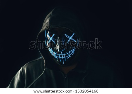 Man with lighting neon glow mask in hood on black background. Halloween and horror concept.