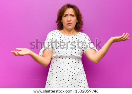 middle age woman looking puzzled, confused and stressed, wondering between different options, feeling uncertain against purple wall #1532059946