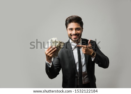 Happy bearded Indian businessman holding fan in hand, Indian Rupee currency bills of 500 , standing isolated over white background #1532122184
