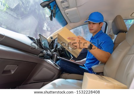 Happy young delivery man holding carton box parcel package. Delivery service courier concept #1532228408
