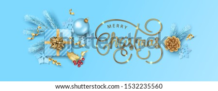 Merry Christmas and New year background. Holiday gift, Christmas decorations, spruce branch and sparkling inscription on a blue background #1532235560