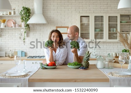 Romantic young couple cooking together in the kitchen, having a great time together. Happy family preparing meal from fresh vegetables. #1532240090