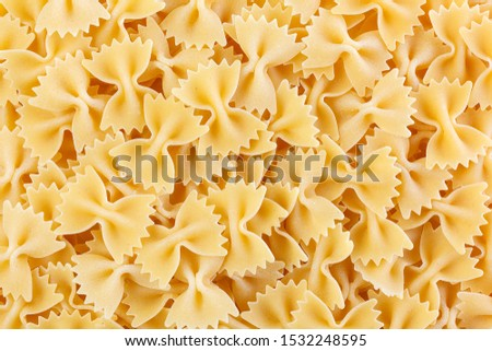 A variety of types and shapes of Italian pasta. Dry pasta bows farfalle.  Heap of bow tie macaroni isolated on white background. #1532248595