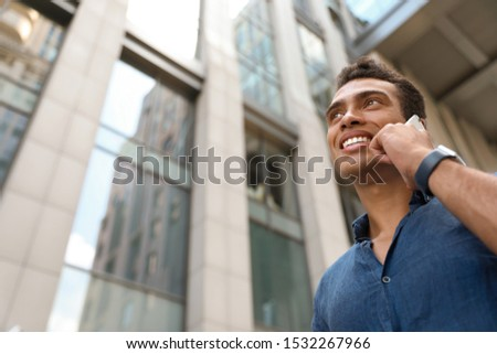 Portrait of handsome young African-American man talking on mobile phone outdoors, low angle view. Space for text #1532267966