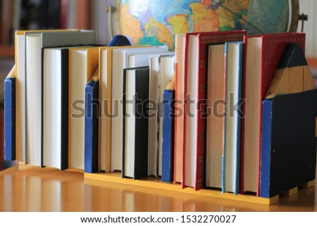 Close-up of several books arranged on a bookshelf in the library. Bookshelf and globe in the background selective focus and shallow depth of field #1532270027