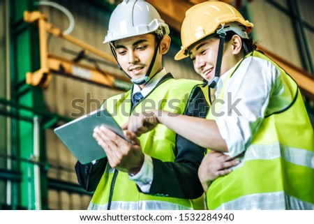 Asian engineer man wearing white helmet with his assistant and using laptop to monitoring the production status. Factory Concept. #1532284940