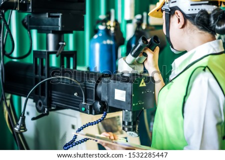 Asian woman is industrial engineer or qc team holding th clipboard while standing in the heavy duty manufacturing shop floor. Factory worker concept. #1532285447