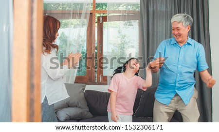 Asian grandparents and granddaughter listen to music and dance together at home. Senior Chinese, grandpa and grandma happy spend family time relax with young girl in living room concept. #1532306171