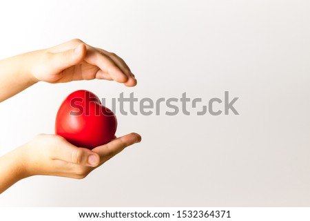 Life in your hands - red heart in child's hands on light background. Medical and health care concept #1532364371